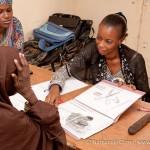 Hopital Lamorde. Hadiza Baoua (responsable observance de Solthis - habit bleu), Mme Abdourahamane Katoumi (accompagnatrice psycho-sociale et vice presidente du groupement  Bafouneye - habit rouge) et Mme Samba Mariama (educatrice therapeutique - habit noir), recoivent une patiente seropositive.