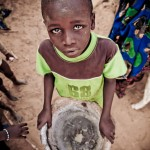 Zongon Maissage, Dakoro Region, Niger, 10 May 2010 - A boy holds an empty mortar used to pound millet. This picture was used by Caritas International on poster and magazine cover.